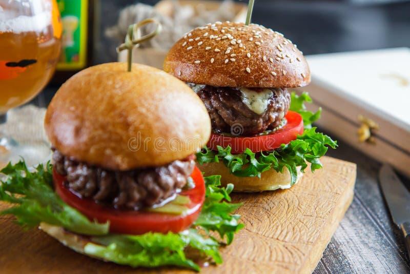 Smaklig och aptitretande hamburgareostburgare på ett träbräde arkivbild