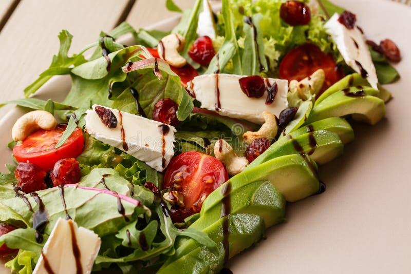 Smaklig och sund sallad med arugula, brien, ost, avokadot, körsbärsröda tomater, den torra tranbäret och kasjuer Top besk?dar _ royaltyfri foto