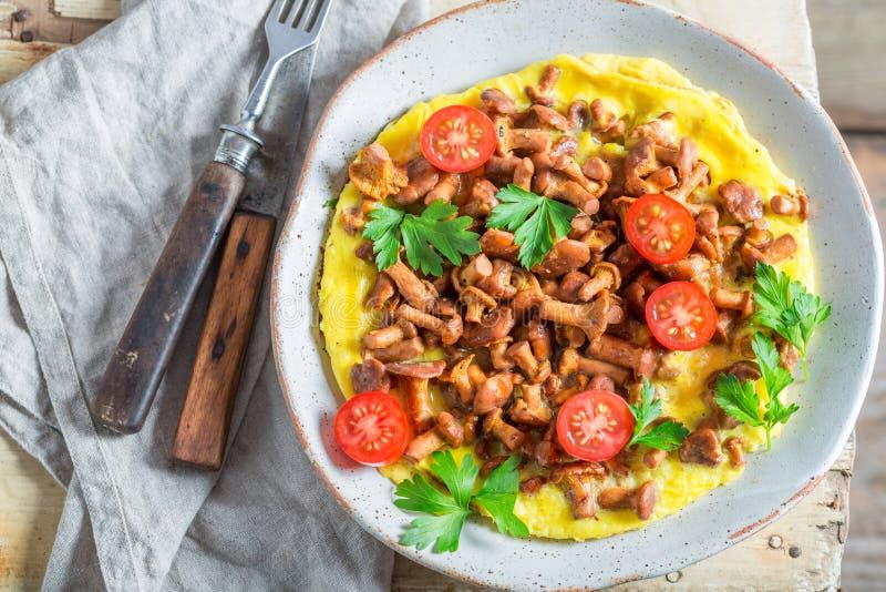 Smaklig omelett som göras av nya kantarellchampinjoner fotografering för bildbyråer