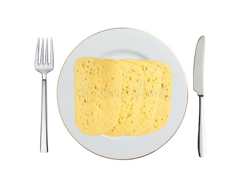 Smaklig ost på den vita den isolerade plattan, kniven och gaffeln royaltyfri bild