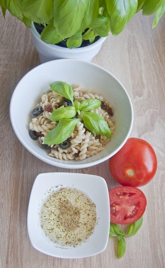 Smaklig pasta med oliv, torkade tomater och den växt- dressingen arkivfoto
