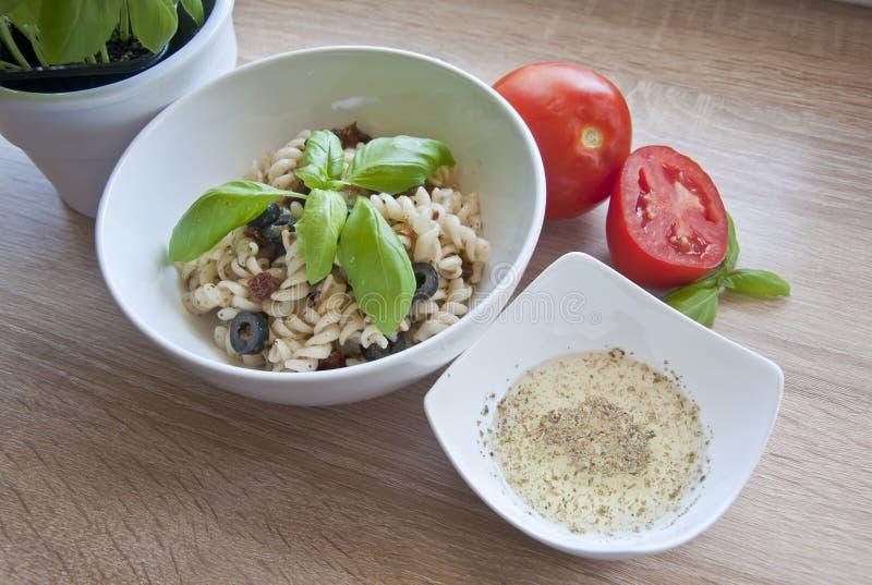 Smaklig pasta med oliv, torkade tomater och den växt- dressingen royaltyfri foto