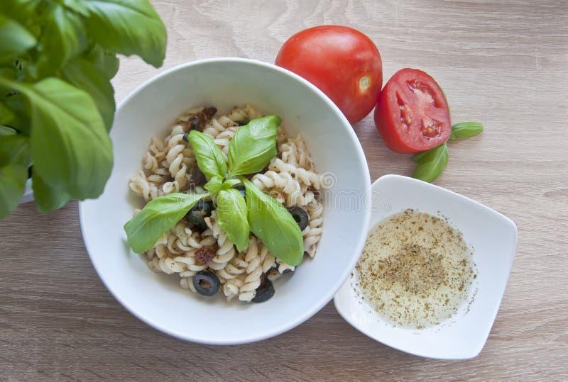Smaklig pasta med oliv, torkade tomater och den växt- dressingen royaltyfri bild