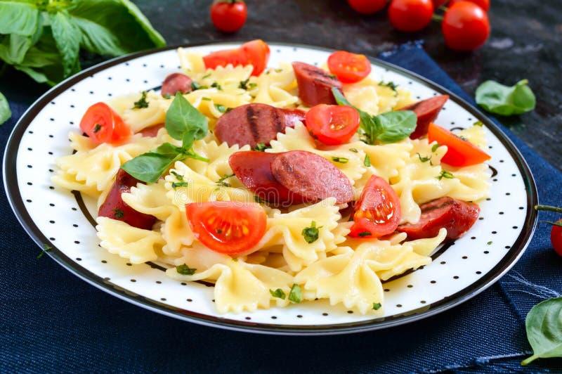 Smaklig pastafarfalle med grillade korvar, nya körsbärsröda tomater och basilika på en platta på en svart bakgrund royaltyfri fotografi