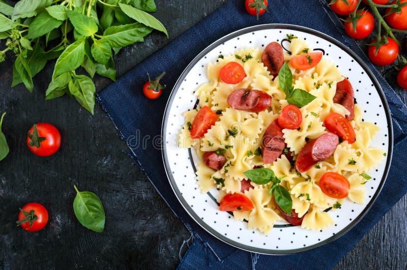 Smaklig pastafarfalle med grillade korvar, nya körsbärsröda tomater och basilika på en platta på en svart bakgrund B?sta sikt, le royaltyfria foton