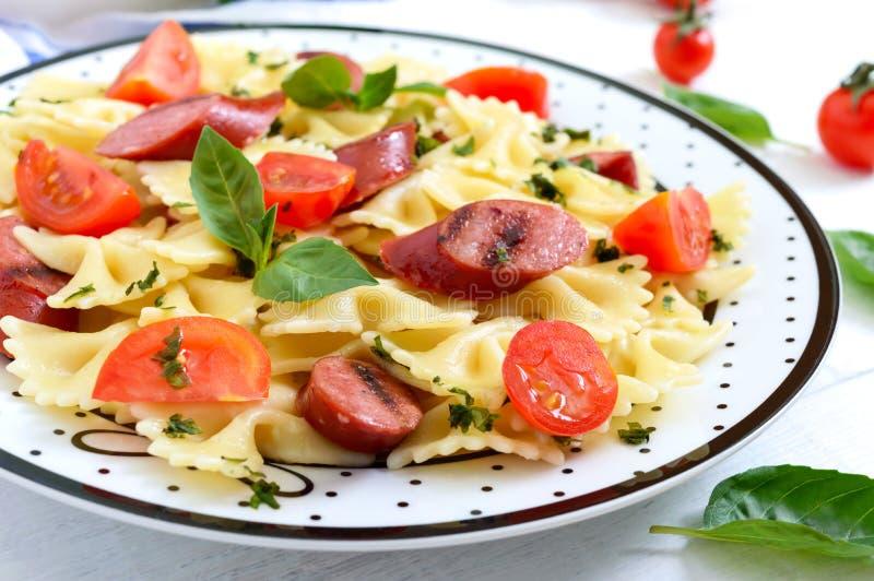 Smaklig pastafarfalle med grillade korvar, nya körsbärsröda tomater och basilika på en platta på en vit träbakgrund royaltyfria bilder