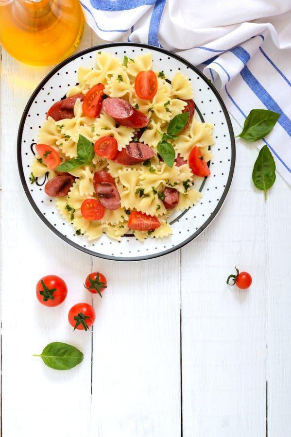 Smaklig pastafarfalle med grillade korvar, nya körsbärsröda tomater och basilika på en platta på en vit träbakgrund b?sta sikt, royaltyfri fotografi