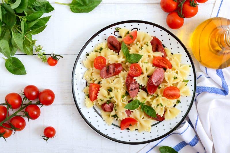 Smaklig pastafarfalle med grillade korvar, nya körsbärsröda tomater och basilika på en platta på en vit träbakgrund b?sta sikt, arkivfoto