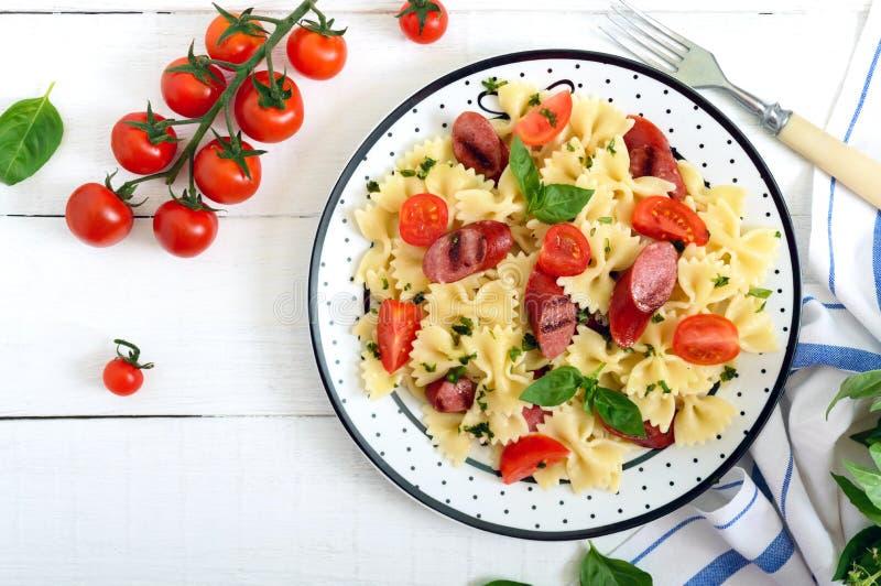Smaklig pastafarfalle med grillade korvar, nya körsbärsröda tomater och basilika på en platta på en vit träbakgrund b?sta sikt, arkivbild