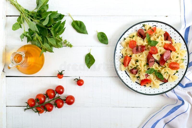 Smaklig pastafarfalle med grillade korvar, nya körsbärsröda tomater och basilika på en platta på en vit träbakgrund b?sta sikt, royaltyfria foton