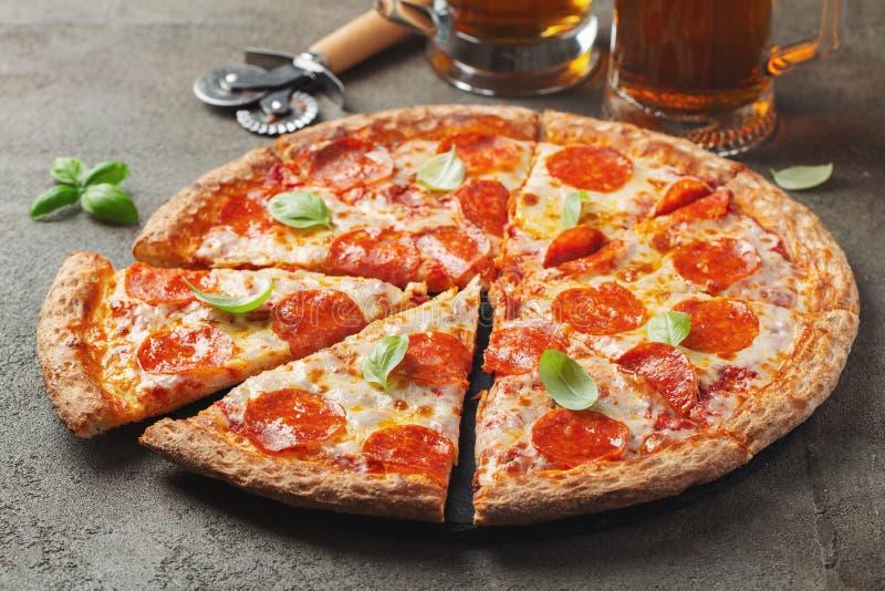 Smaklig peperonipizza med basilika och exponeringsglas av öl på brun konkret bakgrund royaltyfri foto