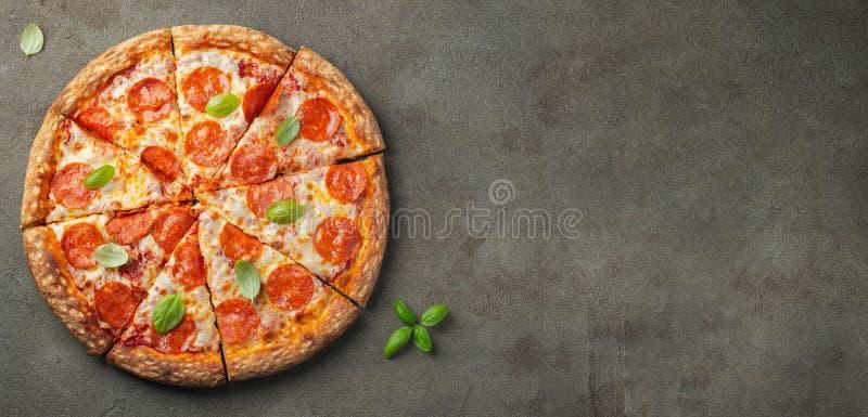 Smaklig peperonipizza med basilika på brun konkret bakgrund Bästa sikt av varm peperonipizza Med kopiera utrymme för text Lekmann royaltyfri bild