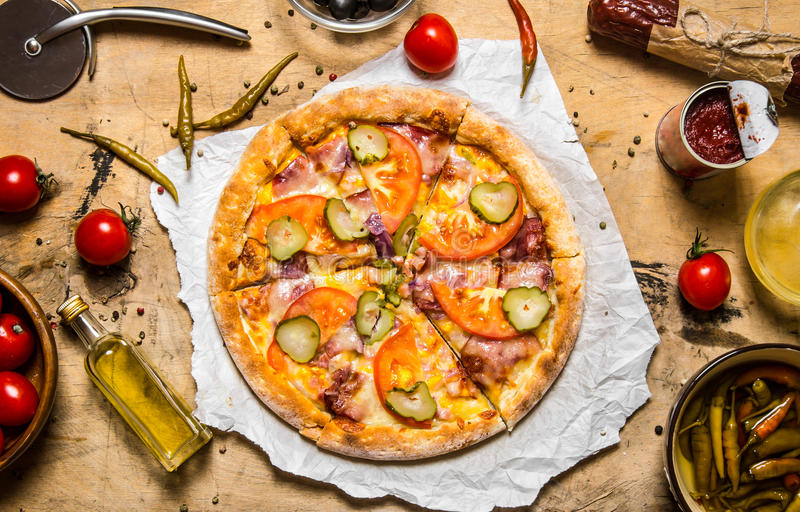 Smaklig pizza med bacon och tomater trägrund tabell för djupfält royaltyfria bilder