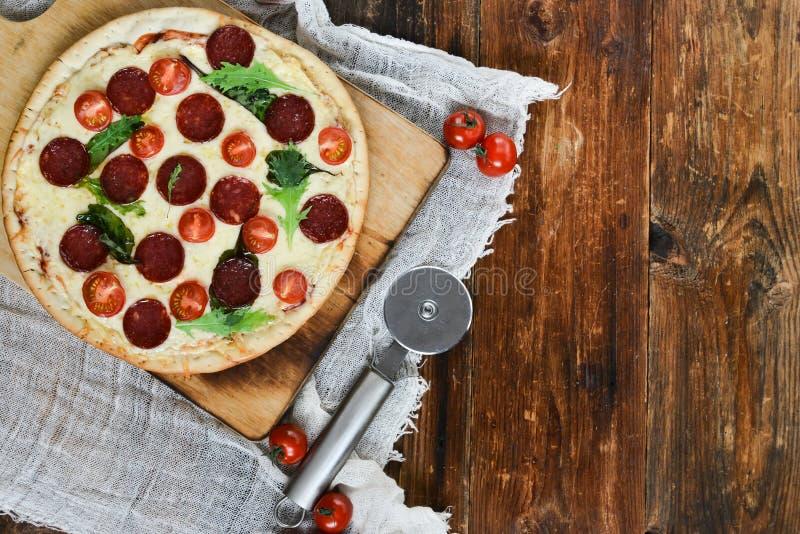 Smaklig pizza med tomatsås, peperonikorven och champinjoner på naturligt lantligt för träbakgrund, en pizzaskärare och en Ingridi arkivbilder