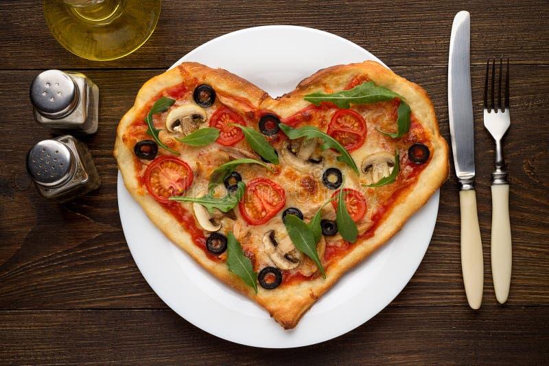 Smaklig varm pizza i hjärtaform med höna och champinjoner och bestick på trätabellen royaltyfria foton