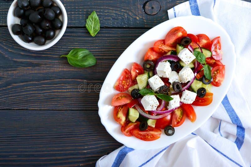 Smaklig vitaminsallad med nya grönsaker, feta, svarta oliv, basilikasås på en vit platta på en träbakgrund Top besk?dar royaltyfria bilder