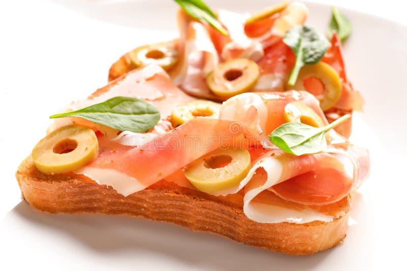 Smakliga bruschettas med oliv och prosciuttoen på plattan, arkivbilder