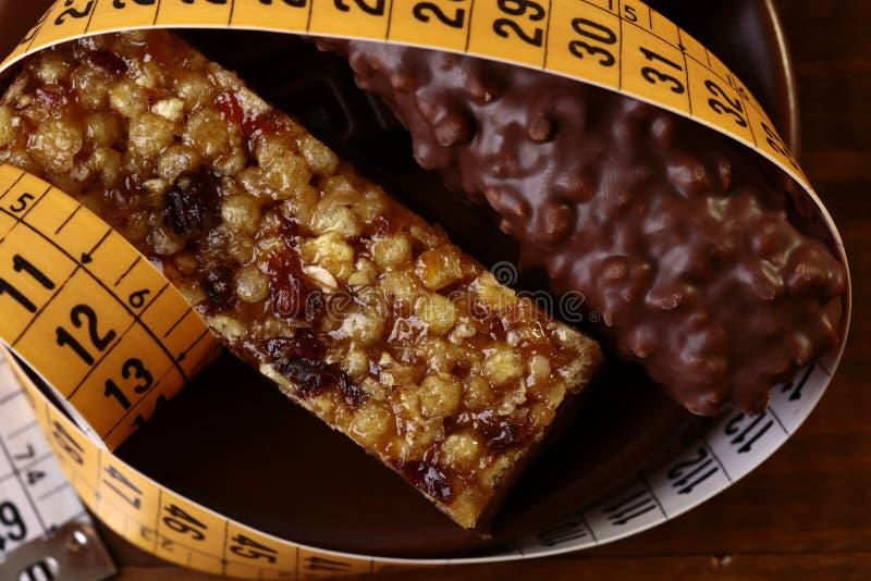 Smakliga chokladstänger och bräckligt för jordnöt med ett mäta band royaltyfri foto