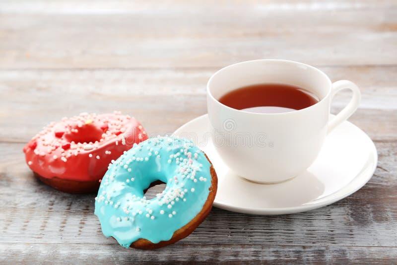 Smakliga donuts och kopp te arkivbild