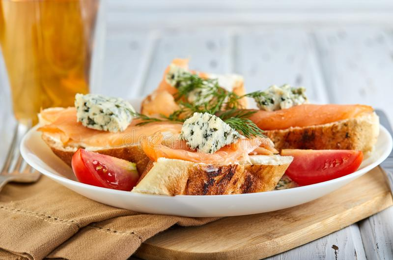 Smakliga frukostsmörgåsar med laxen och ost och körsbärsröda tomater på en trävit royaltyfri fotografi