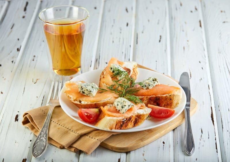 Smakliga frukostsmörgåsar med laxen och ost och körsbärsröda tomater på en trävit arkivbilder