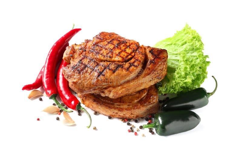 Smakliga grillade biffar med nya grönsaker på vit bakgrund royaltyfri bild