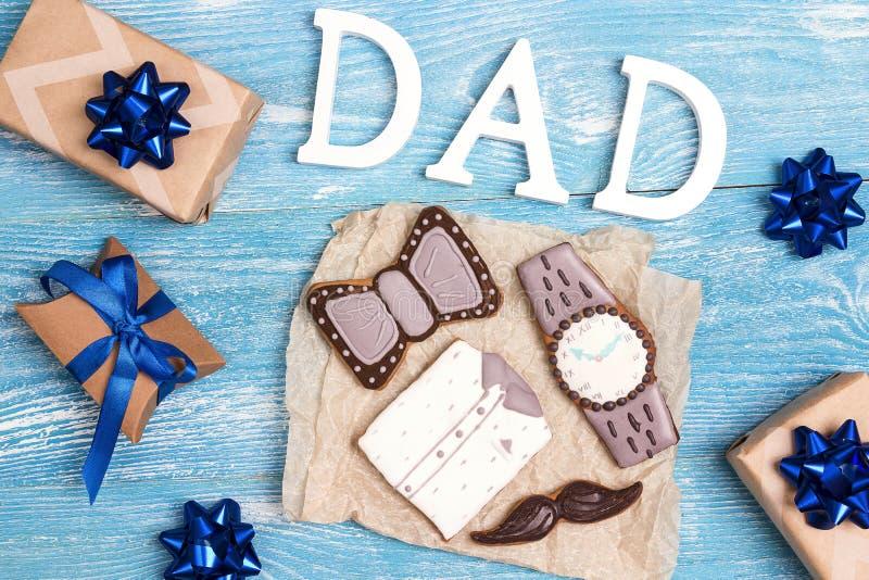 Smakliga idérika kakor med ordfarsa- och gåvaaskar på blå träbakgrund Pepparkaka i formen av en skjorta, klocka, fluga arkivbild