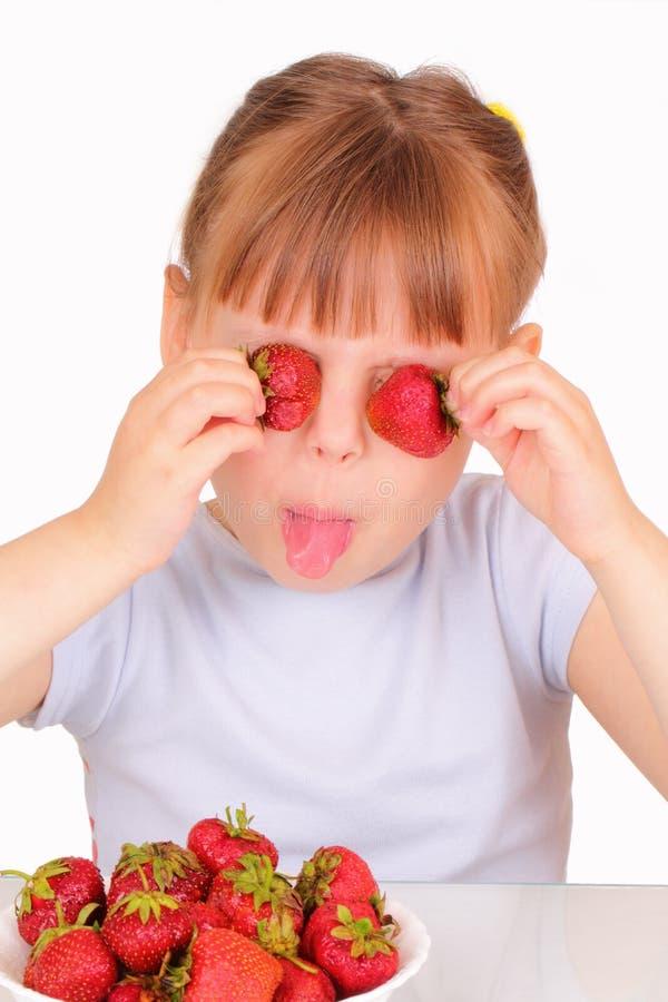 smakliga lilla jordgubbar för rolig flicka royaltyfria foton