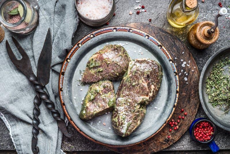 Smakliga marinera köttbiffar med örter och kryddor för galler eller grillfest på köksbordet med rostfritt stål på lantligt kök t royaltyfri fotografi