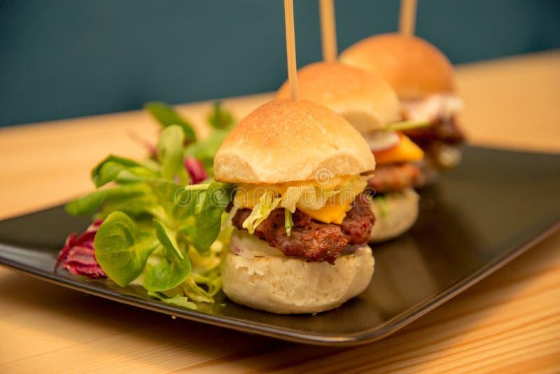 Smakliga mini- hamburgare för närbild med sallad på bistrotabellen royaltyfri foto