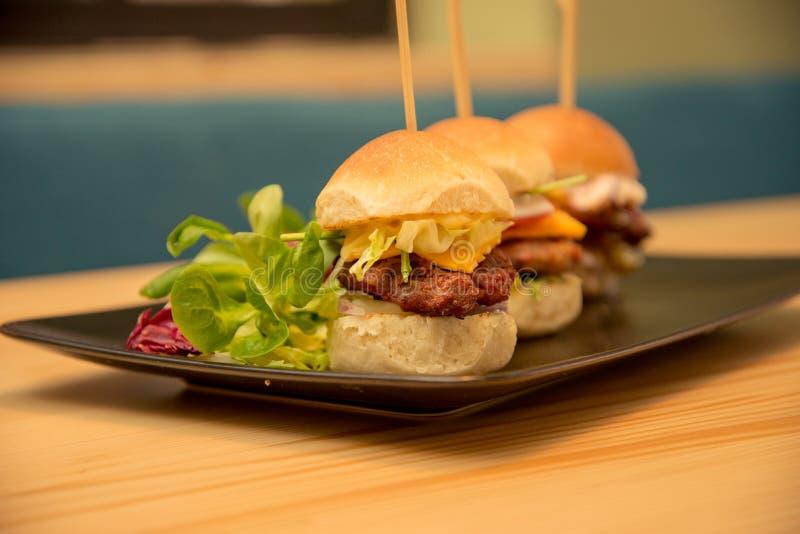 Smakliga mini- hamburgare f?r n?rbild med sallad p? bistrotabellen royaltyfria bilder