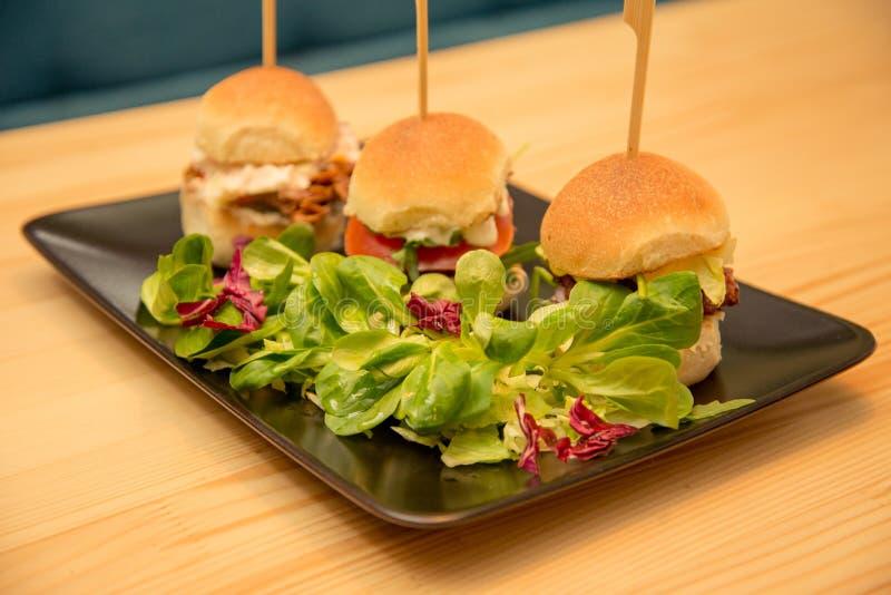 Smakliga mini- hamburgare f?r n?rbild med sallad p? bistrotabellen arkivbilder