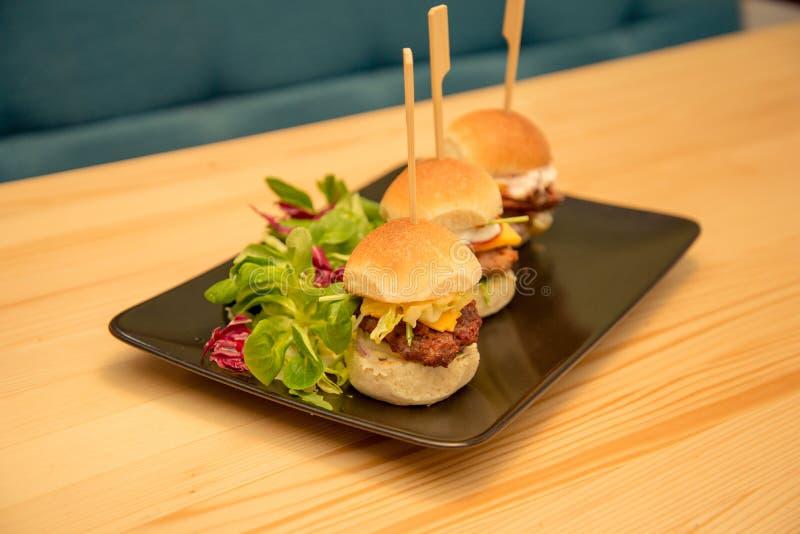 Smakliga mini- hamburgare med sallad på bistrotabellen arkivfoton