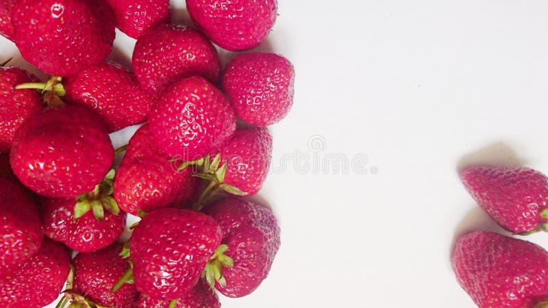 Smakliga mogna röda jordgubbar i sommar på en vit bakgrund arkivbilder