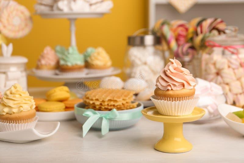 Smakliga muffin och andra sötsaker på tabellen Godisst?ng royaltyfri foto
