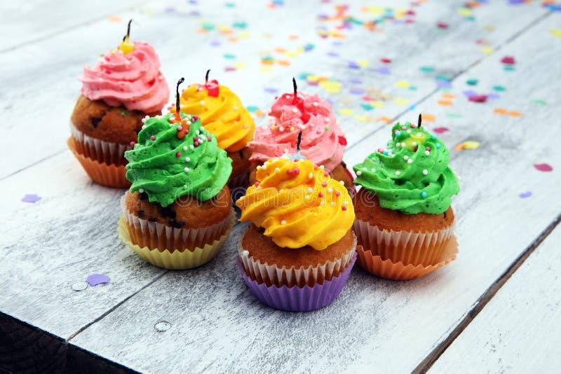 Smakliga muffin på träbakgrund Födelsedagmuffin i regnbåge royaltyfri foto
