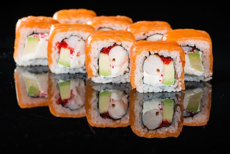 Smakliga nya sushirullar med ris, gräddost, räkor, avocad royaltyfri fotografi