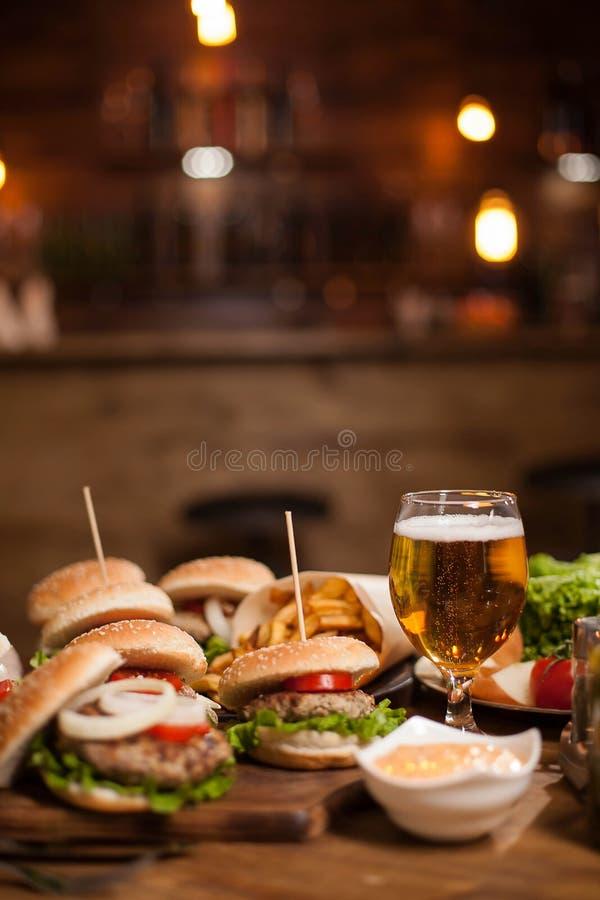 Smakliga olika hamburgare och ett exponeringsglas av kallt öl på trätabellen fotografering för bildbyråer