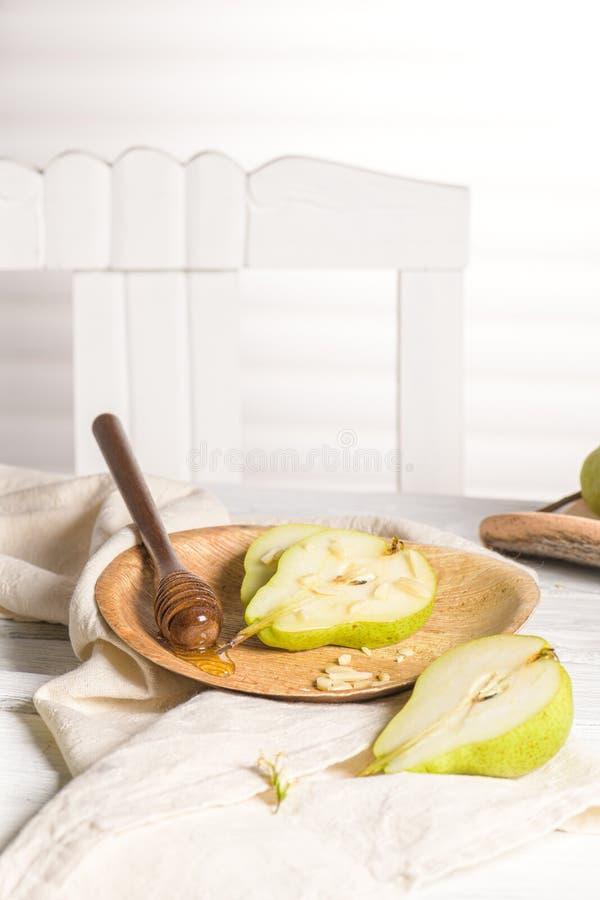 Smakliga päron med honung och muttrar arkivbild
