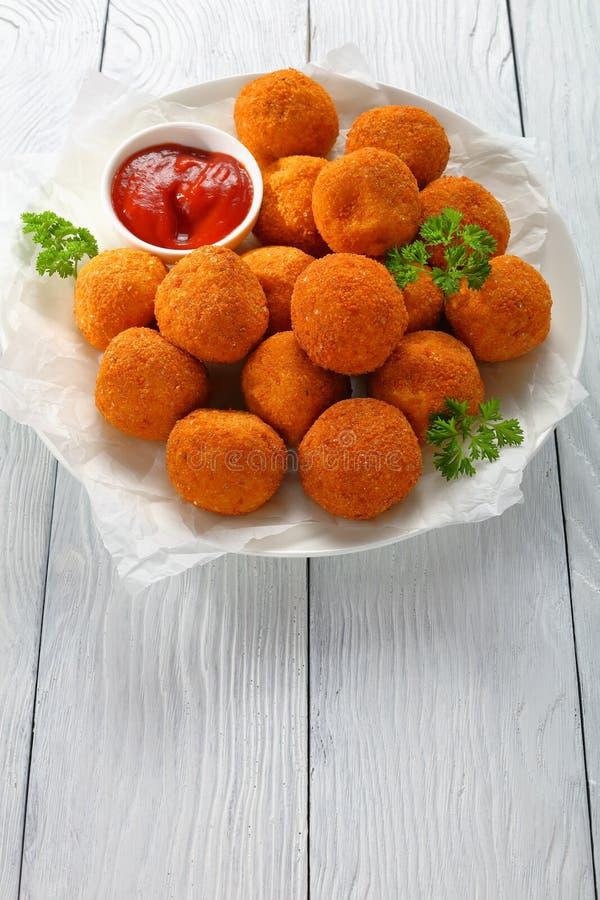 Smakliga potatiskroketter - mosade potatisar klumpa ihop sig bröat och som steker djupt, tjänat som med ketchup på den vita platt arkivbilder