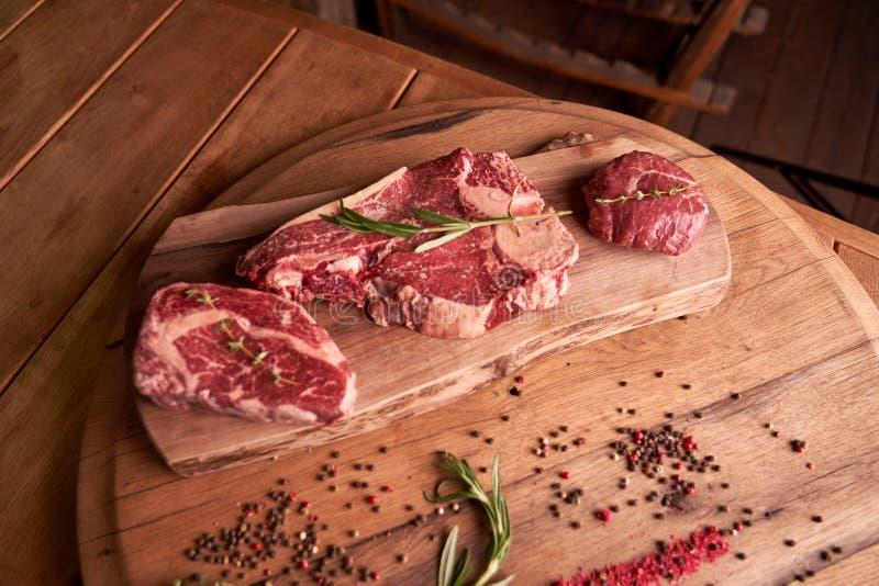 Smakliga rå biffar av stödögat kryddade nötköttkött på en skärbräda på en träbakgrund med en kvist av rosmarin, pepparkorn arkivfoto