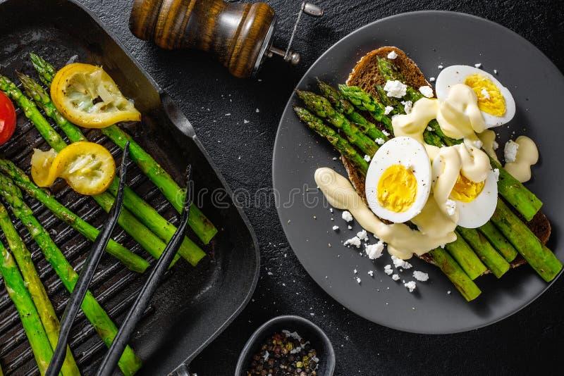 Smakliga rostade bröd med sparriers, ägg och sås royaltyfri foto