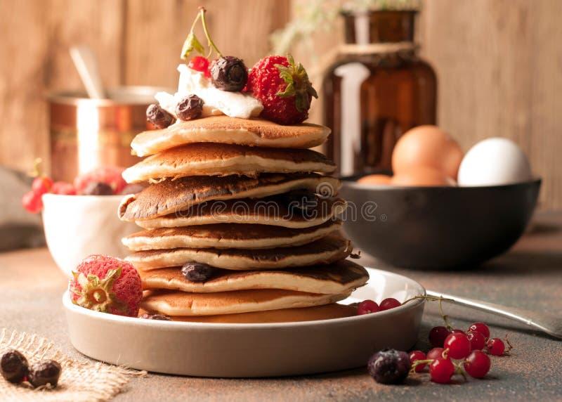 smakliga traditionella amerikanska pannkakor i bunt med gräddfil, nya bär på den vita plattan nära bunken med rå bruna ägg och gl royaltyfria foton