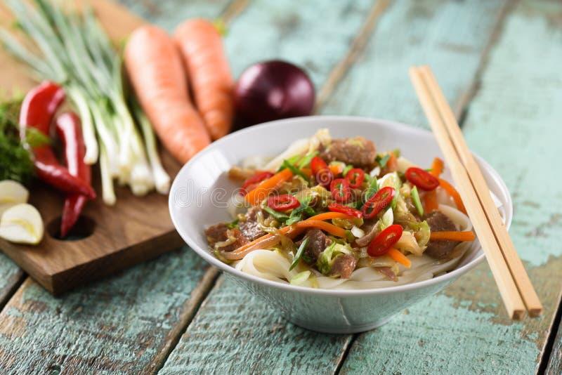 Smakliga traditionella asiatiska nudlar med kött och grönsaker i whit royaltyfri foto