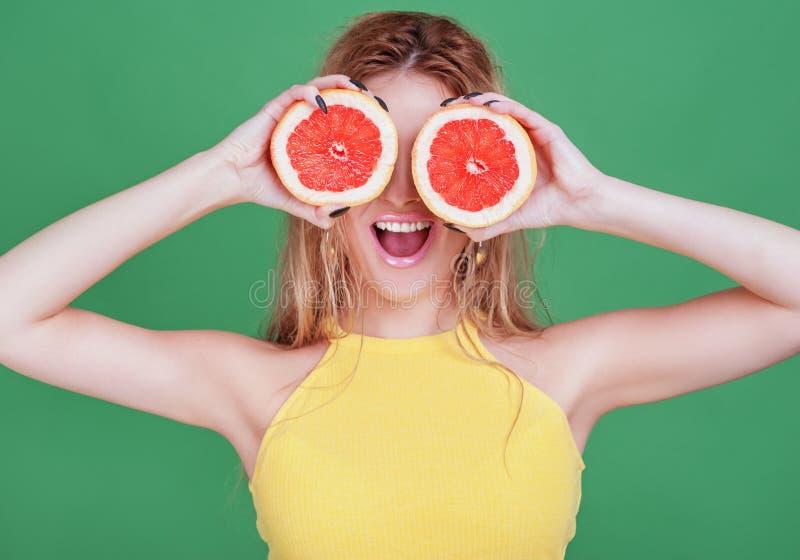 Smakliga tropiska frukter! Attraktiv sexuell kvinna med härlig makeup som rymmer den nya saftiga grapefrukten eller den orange ne arkivfoto