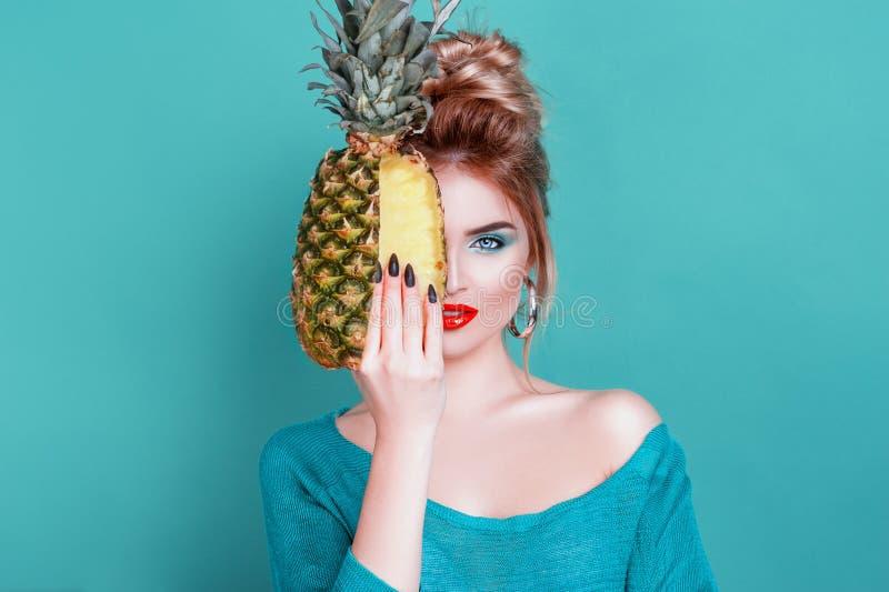 Täckta tropiska frukter! En attraktiv sexuell kvinna med en vacker smink som håller färsk juicy pineapple och tittar på kameran royaltyfri bild