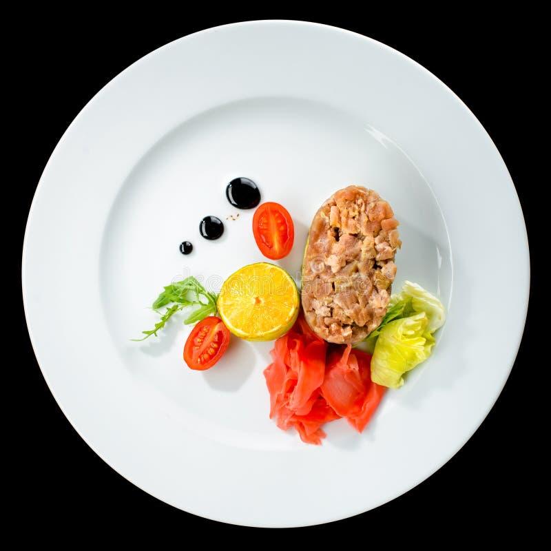 Smakliga Tuna Tartare med limefrukt, ingefäran och avokadot i en vit plat arkivfoto