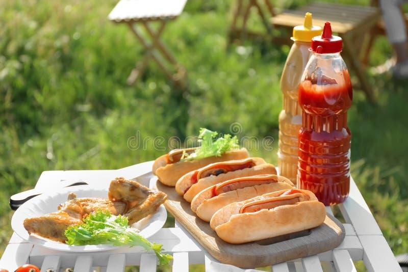 Smakliga varmkorvar och platta med grillade fega vingar på tabellen utomhus Trevlig ny mat och korg p? gr?set royaltyfri bild