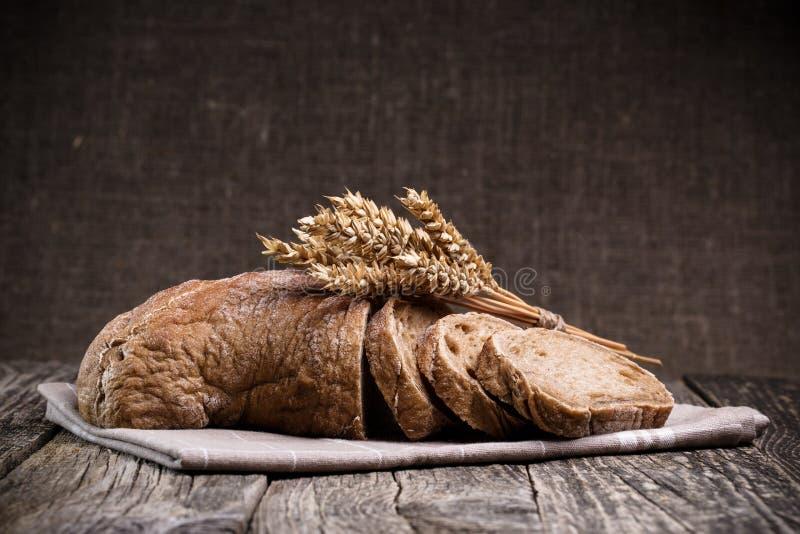 Smakligt bröd med vete på träbakgrund royaltyfria foton