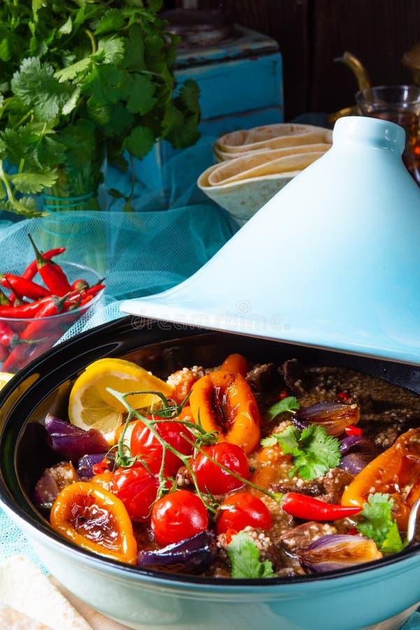 Smakligt kryddigt nötkött med olika grönsaker som lagas mat i tagine royaltyfria foton